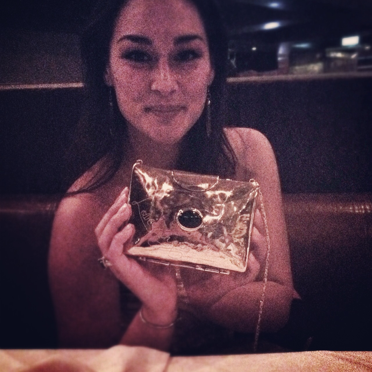 woman holding gold clutch